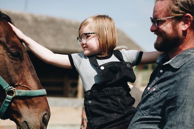 Petite fille caresse un cheval