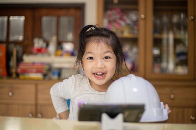 Petite fille avec casque blanc ingénieur à la maison