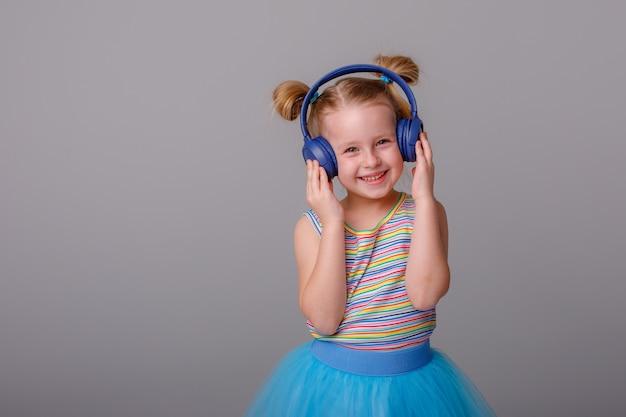 Une petite fille avec un casque d'écoute de la musique sur un espace blanc