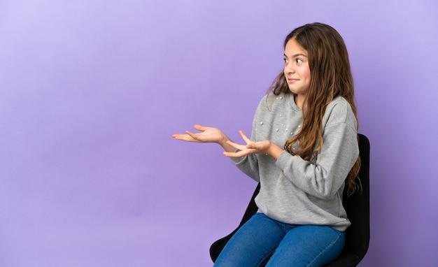 Petite fille caucasienne assise sur une chaise isolée sur fond violet avec une expression surprise tout en regardant de côté