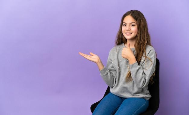 Petite fille caucasienne assise sur une chaise isolée sur fond violet tenant un espace de copie imaginaire sur la paume pour insérer une annonce et avec les pouces vers le haut
