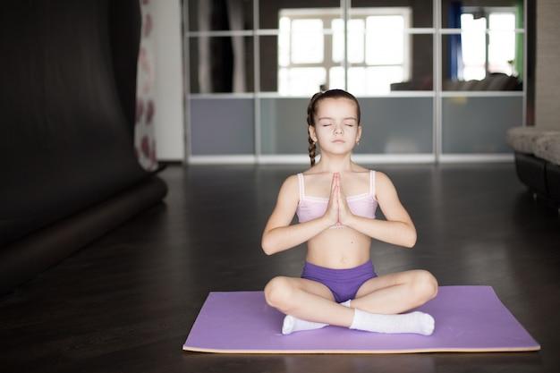 Petite fille caucasienne assise sur un tapis dans la pose d'yoga et méditant.