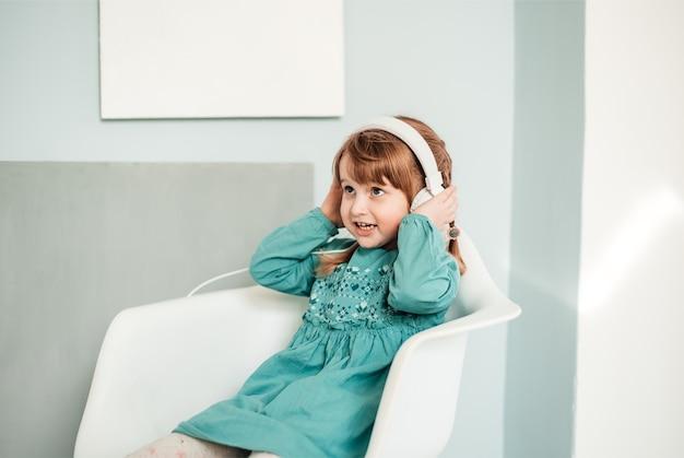 Une petite fille caucasienne au casque blanc écoute de la musique et danse dans une robe bleue turquoise lumineuse.