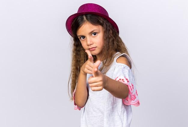Petite fille caucasienne confiante avec un chapeau de fête violet pointant isolé sur un mur blanc avec espace de copie