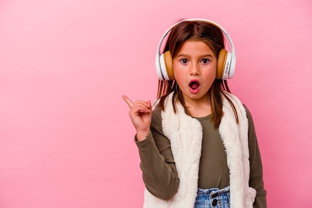 Petite fille caucasienne écoutant de la musique isolée sur fond rose pointant vers le côté