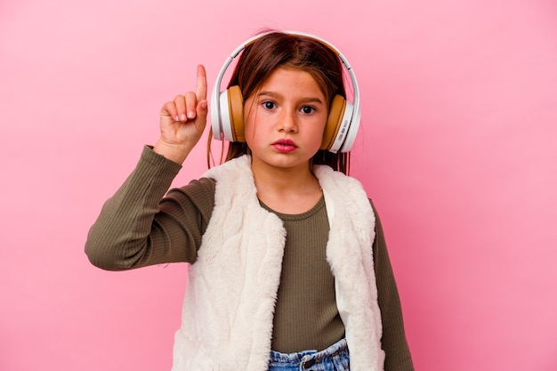 Petite fille caucasienne écoute de la musique isolée sur un mur rose ayant une excellente idée, concept de créativité.