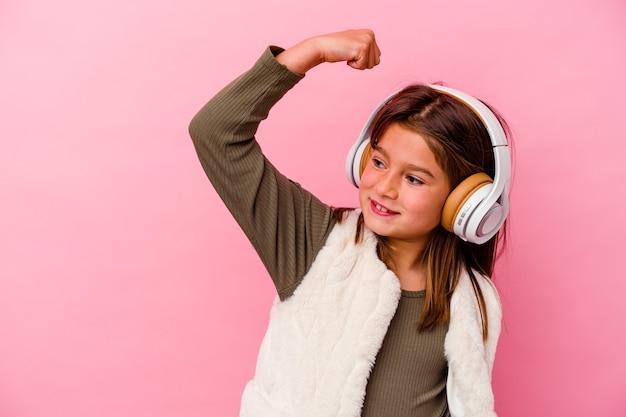 Petite fille caucasienne écoute de la musique isolée sur un mur rose en levant le poing après une victoire, concept gagnant.