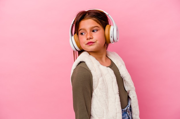 Petite fille caucasienne écoute de la musique isolée sur un mur rose regarde de côté souriant, gai et agréable.