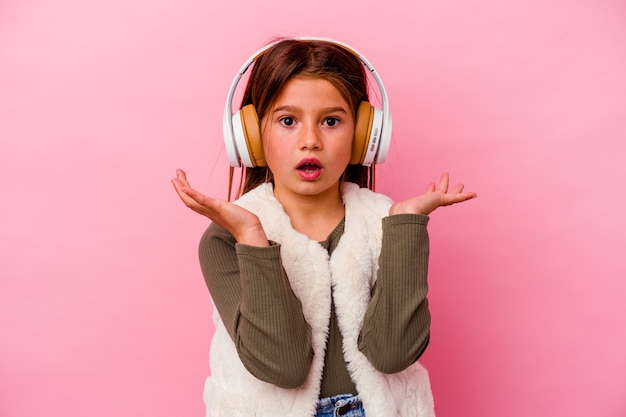 Petite fille caucasienne écoute de la musique isolée sur un mur rose surpris et choqué.