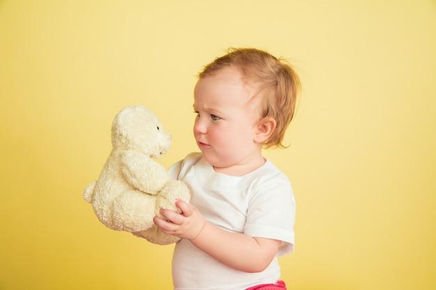 Petite fille caucasienne, enfants isolés sur fond de studio jaune. portrait d'enfant mignon et adorable, bébé jouant avec l'ours en peluche. concept d'enfance, de famille, de bonheur, de nouvelle vie, d'éducation.