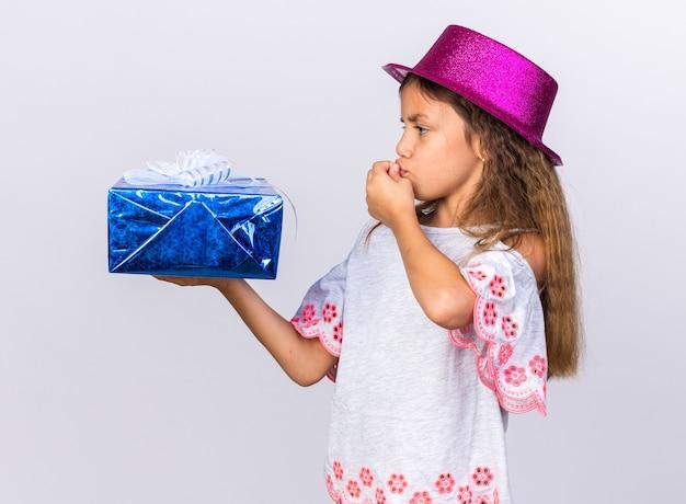 Petite fille caucasienne excitée avec un chapeau de fête violet tenant une boîte-cadeau et embrassant des doigts isolés sur un mur blanc avec un espace de copie