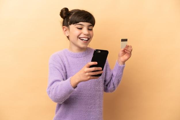 Petite fille caucasienne isolé acheter avec le mobile avec une carte de crédit