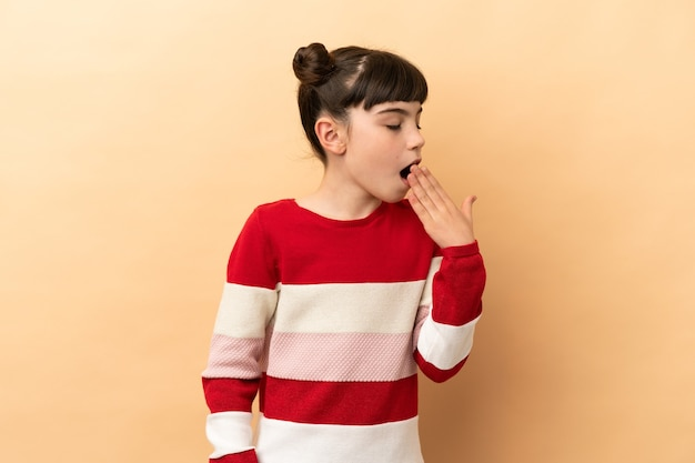 Petite fille caucasienne isolée sur le bâillement beige et couvrant la bouche grande ouverte avec la main