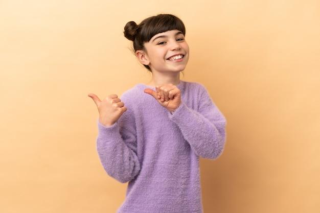Petite fille caucasienne isolée sur beige pointant vers le côté pour présenter un produit