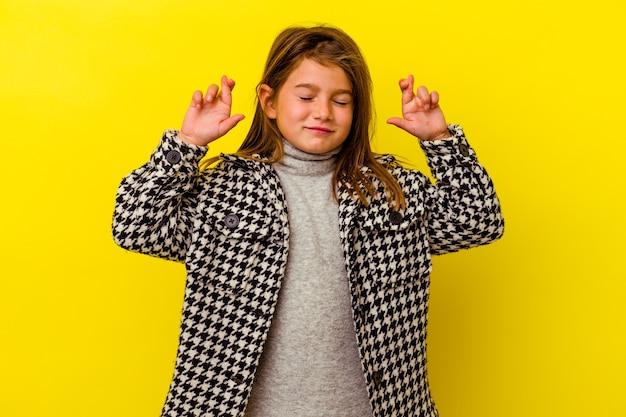 Petite fille caucasienne isolée sur les doigts croisés jaunes pour avoir de la chance