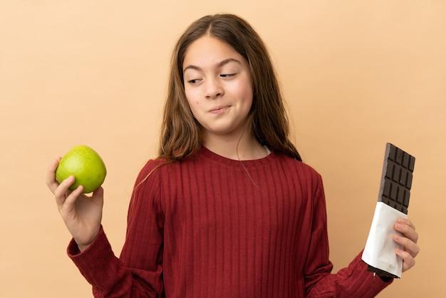 Petite fille caucasienne isolée sur fond beige ayant des doutes en prenant une tablette de chocolat dans une main et une pomme dans l'autre