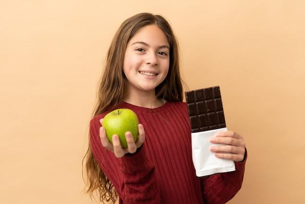 Petite fille caucasienne isolée sur fond beige prenant une tablette de chocolat dans une main et une pomme dans l'autre