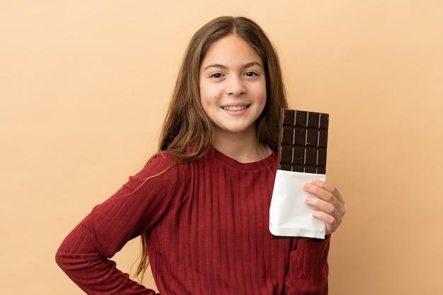 Petite fille caucasienne isolée sur fond beige prenant une tablette de chocolat et heureuse