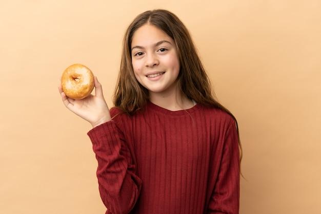 Petite fille caucasienne isolée sur fond beige tenant un beignet et heureux