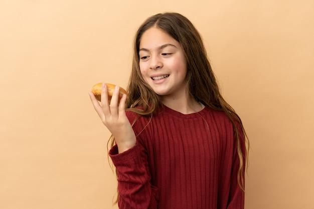 Petite fille caucasienne isolée sur fond beige tenant des beignets avec une expression heureuse