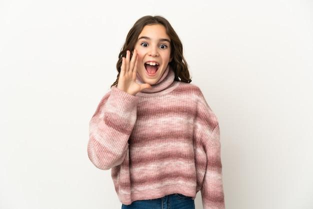 Petite fille caucasienne isolée sur fond blanc avec une expression faciale surprise et choquée