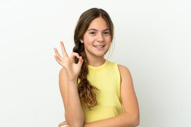 Petite fille caucasienne isolée sur fond blanc montrant un signe ok avec les doigts