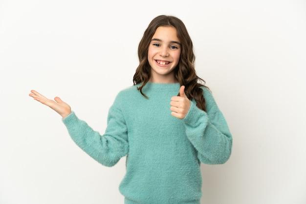 Petite fille caucasienne isolée sur fond blanc tenant un espace de copie imaginaire sur la paume pour insérer une annonce et avec les pouces vers le haut