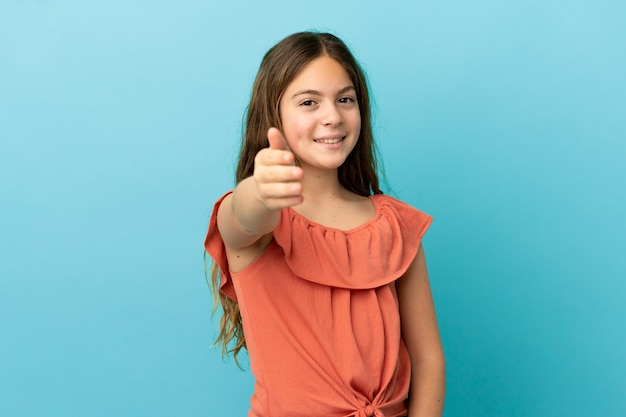 Petite fille caucasienne isolée sur fond bleu se serrant la main pour conclure une bonne affaire