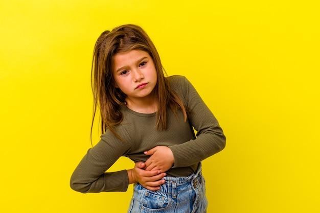Petite fille caucasienne isolée sur fond jaune ayant une douleur au foie, des maux d'estomac.
