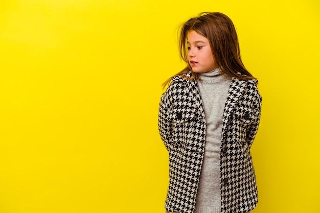 Petite fille caucasienne isolée sur fond jaune choquée à cause de quelque chose qu'elle a vu.