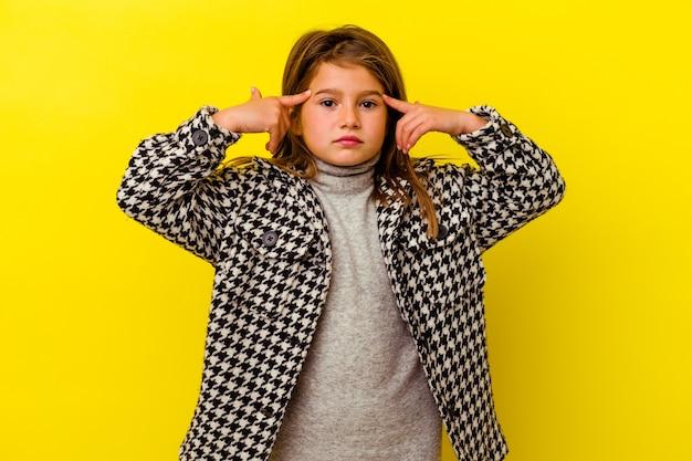 Petite fille caucasienne isolée sur fond jaune concentrée sur une tâche, gardant les index pointant la tête.