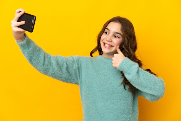 Petite fille caucasienne isolée sur fond jaune faisant un selfie avec un téléphone portable