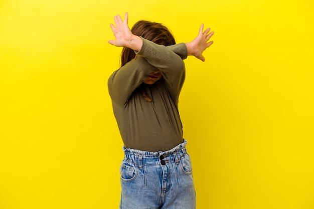 Petite fille caucasienne isolée sur fond jaune en gardant les deux bras croisés, concept de déni.