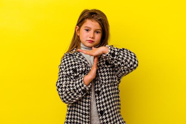 Petite fille caucasienne isolée sur fond jaune montrant un geste de délai d'attente.