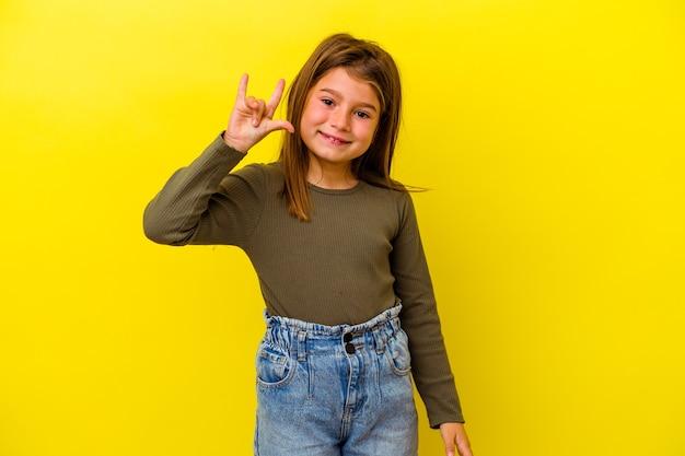 Petite fille caucasienne isolée sur fond jaune montrant un geste rock avec les doigts