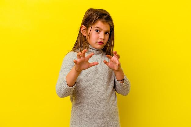 Petite fille caucasienne isolée sur fond jaune montrant des griffes imitant un chat, geste agressif.