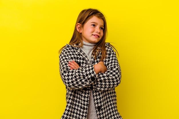 Petite fille caucasienne isolée sur fond jaune rêvant d'atteindre des objectifs et des buts