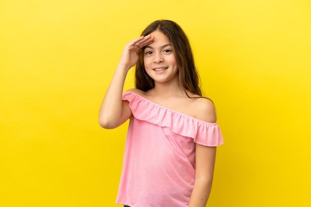 Petite fille caucasienne isolée sur fond jaune saluant avec la main avec une expression heureuse