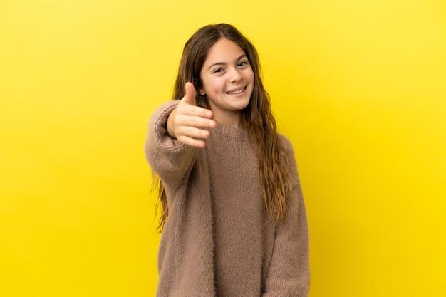Petite fille caucasienne isolée sur fond jaune se serrant la main pour conclure une bonne affaire