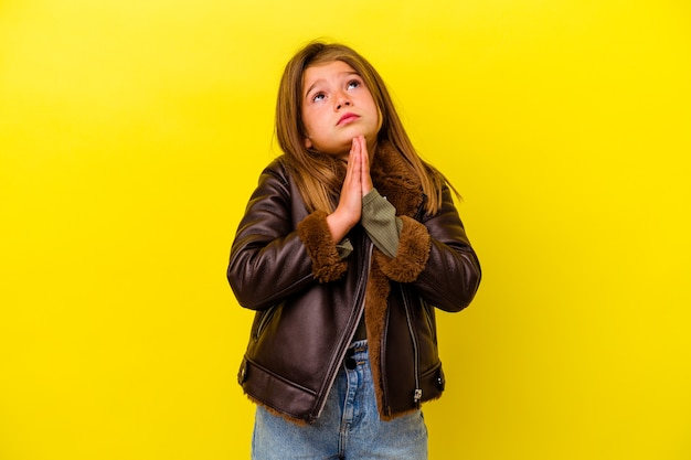Petite fille caucasienne isolée sur fond jaune tenant la main en prière près de la bouche, se sent confiante.