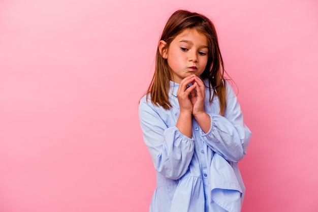 Petite fille caucasienne isolée sur fond rose, élaboration d'un plan en tête, mise en place d'une idée.