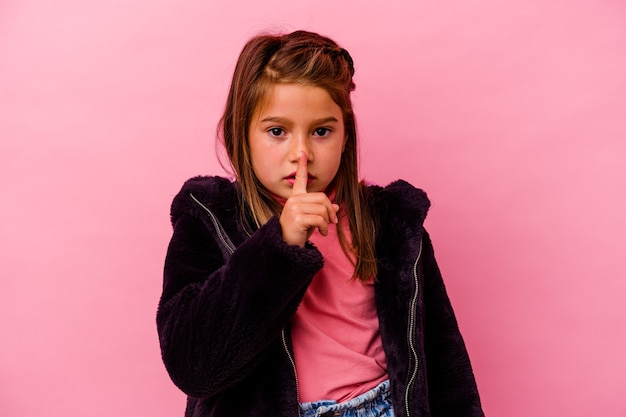 Petite fille caucasienne isolée sur fond rose gardant un secret ou demandant le silence.