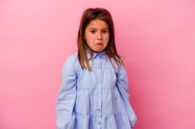 Petite fille caucasienne isolée sur fond rose hausse les épaules et ouvre les yeux confus.
