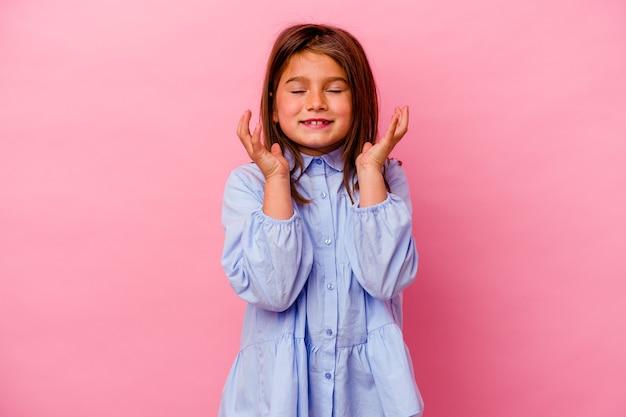 Petite fille caucasienne isolée sur fond rose joyeux riant beaucoup. notion de bonheur.