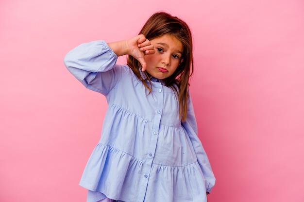 Petite fille caucasienne isolée sur fond rose montrant un geste d'aversion, les pouces vers le bas. notion de désaccord.
