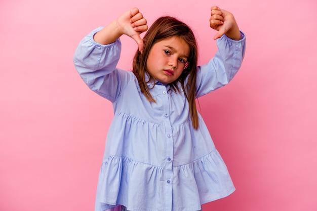 Petite fille caucasienne isolée sur fond rose montrant le pouce vers le bas et exprimant son aversion.