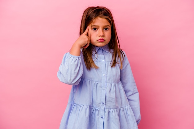 Petite fille caucasienne isolée sur fond rose pointant le temple avec le doigt, pensant, concentrée sur une tâche.