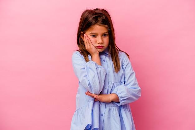 Petite fille caucasienne isolée sur fond rose qui s'ennuie, est fatiguée et a besoin d'une journée de détente.
