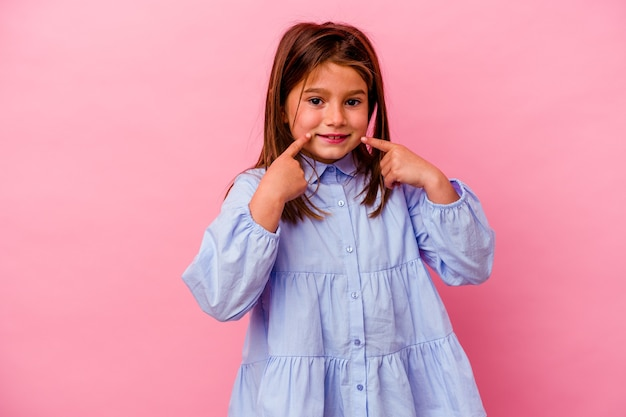 Petite fille caucasienne isolée sur fond rose sourit, pointant du doigt la bouche.
