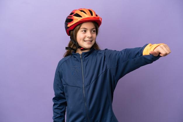 Petite fille caucasienne isolée sur fond violet donnant un geste du pouce vers le haut